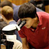 Summers of Discovery student using microscope