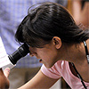 A teen girl looks into a microscope