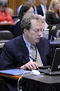Feinberg referencing materials on his laptop during the presentatiion