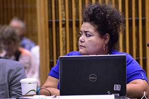 Elizabeth Yeampierre sitting with her laptop listening to the council meeting