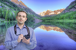 Tolun standing with his digital camera in front of a scenic lake with mountains