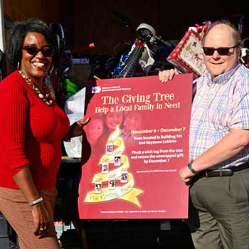 Volunteers holing the Giving Tree poster behind a truck filled with donated gifts