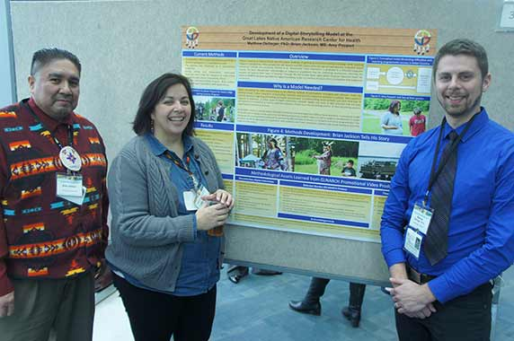 Brian Jackson, Amy Poupart and Matthew Dellinger, Ph.D. standing in front of their poster of the Development of a Digital Storytelling Model at the Great Lakes Native American Research Center for Health