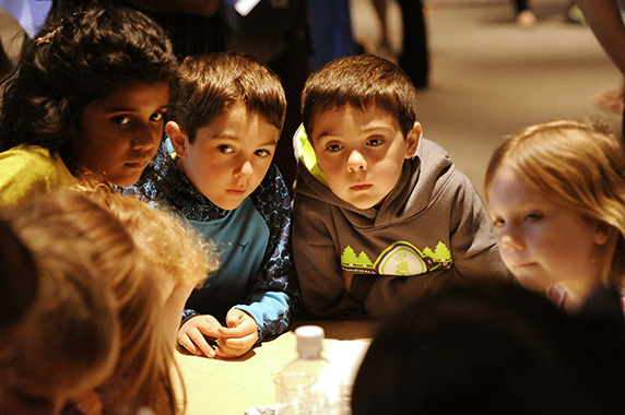 Children gathered around a table paying close attention to what the scientists were telling them