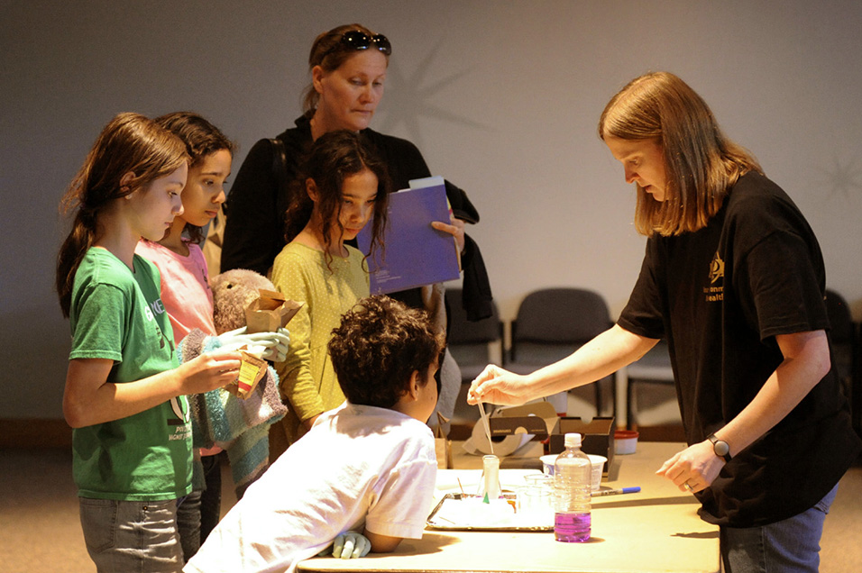 Abee Bowles teaches children that are gathered around her table about chemicals