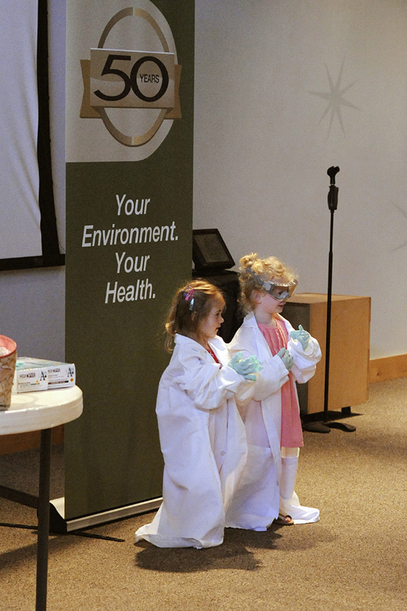 Two young girls dressed in lab coats and goggles, ready to be scientists