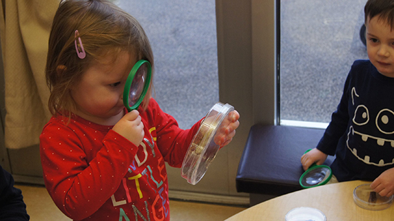 Handling petri dishes and magnifying glasses is routine at the learning center, which helps develop an early love of scientific inquiry in its young clients.