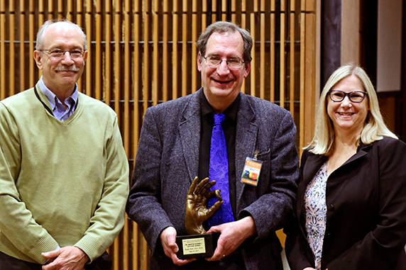 NIEHS Deputy Director Richard Woychik, Ph.D., left, and Dudek, right, presented Roth with the Rodbell Lecture statue following the seminar.