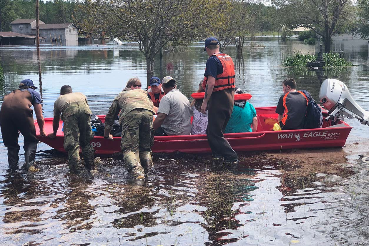Members of the U.S. Coast Guard and North Carolina National Guard push a boat full of residents in flood waters.