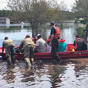 military personnel push a boat full of residents through flooded streets