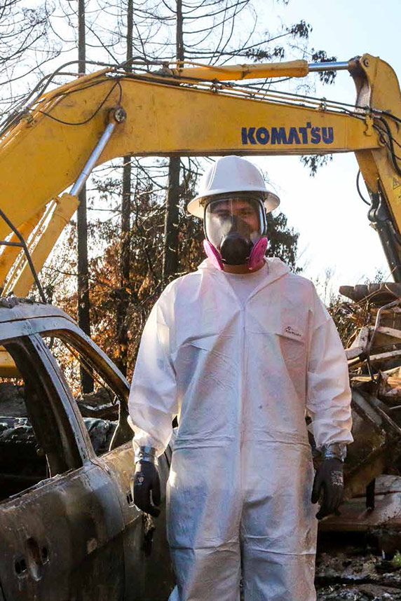 Wildfire cleanup worker wearing full protective suit