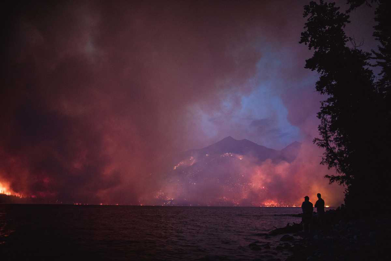 wildfire burns mountains overlooking lake