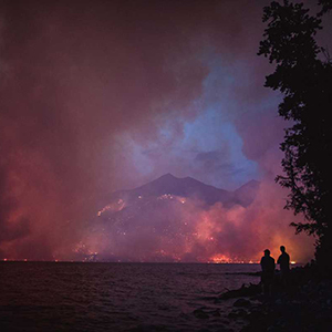 wildfire burning mountains overlooking lake