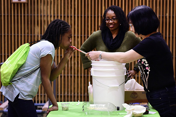 girl and scientists doing a lung capacity demonstration