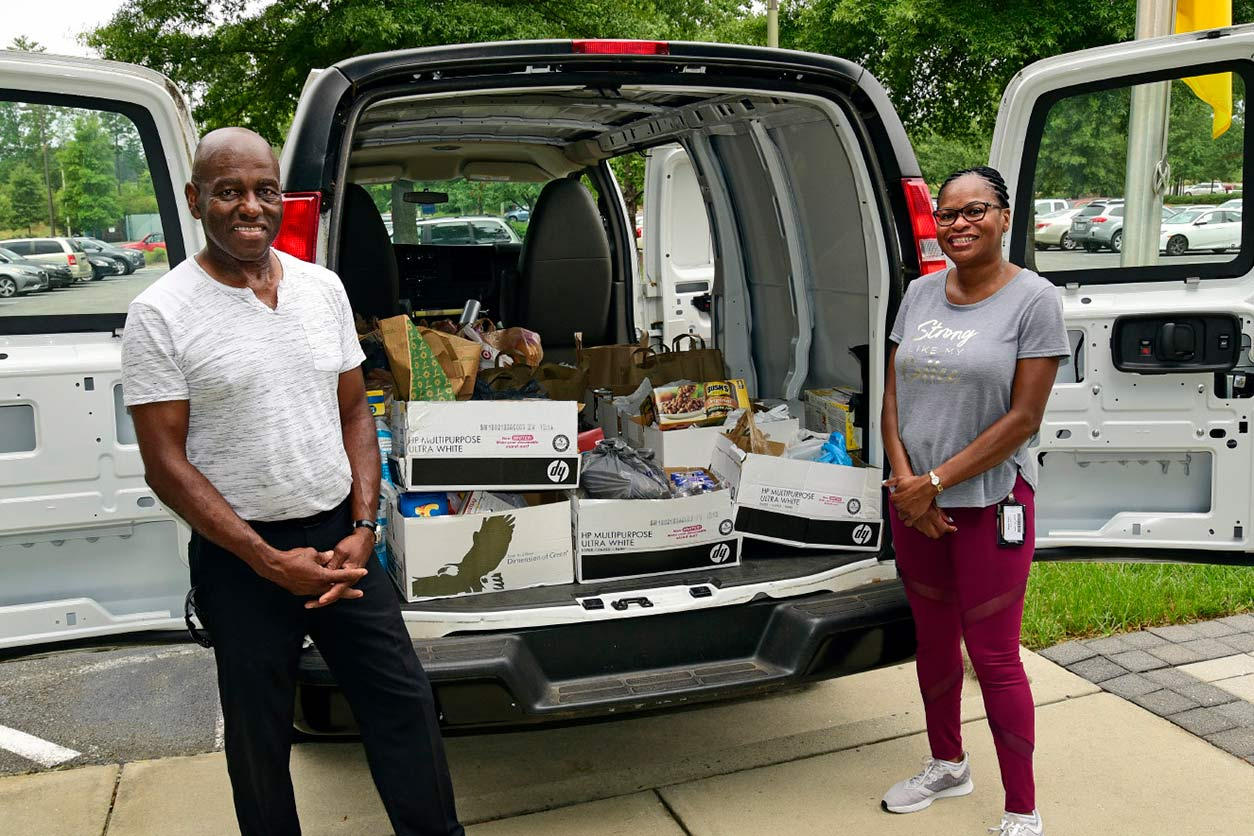Wilder and Brace pose next to the van-full of donated food items
