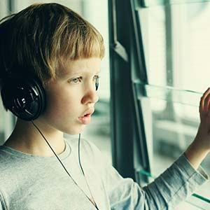 Boy looking out window with headphones over ears