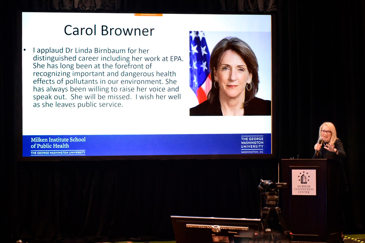 Lynn Goldman, M.D. standing at podium with Carol Browner, J.D. shown on a projection screen with a message of goodwill
