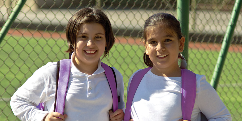 2 young girls smiling at the camera
