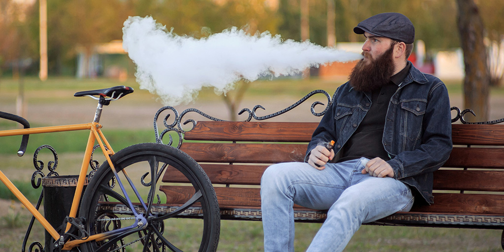 man sitting on bench next to a bicycle exhaling a large cloud of smoke