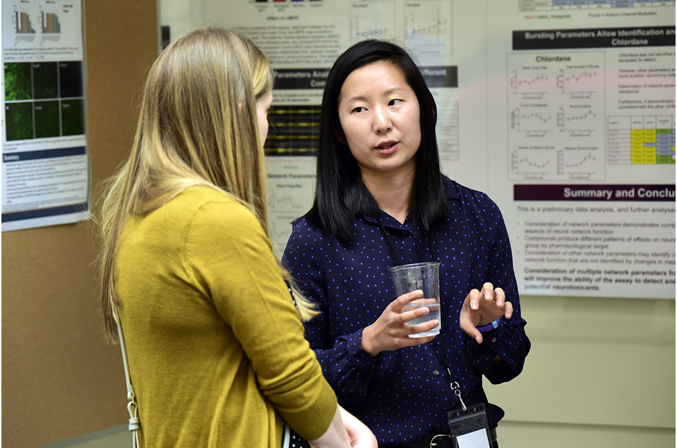 Mimi Huang, Ph.D. speaking with an attendee