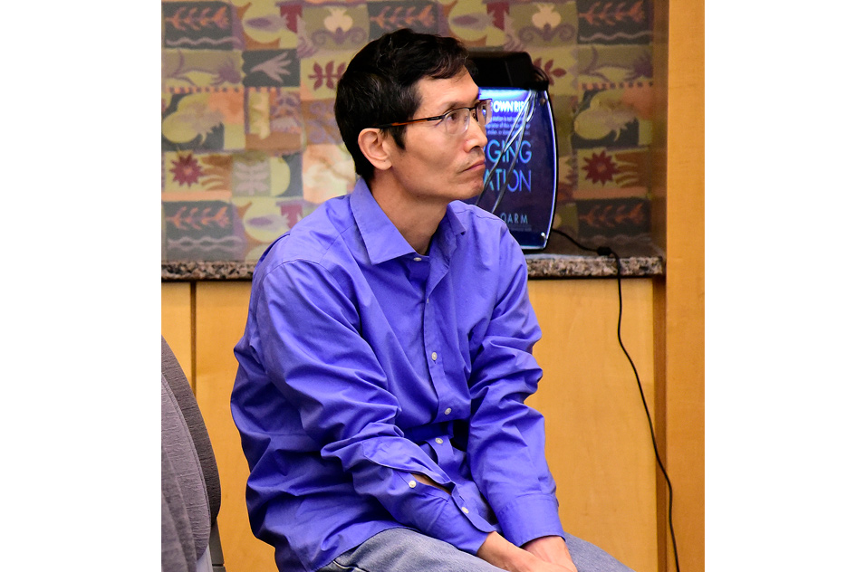 Leping Li, Ph.D. listens while seated