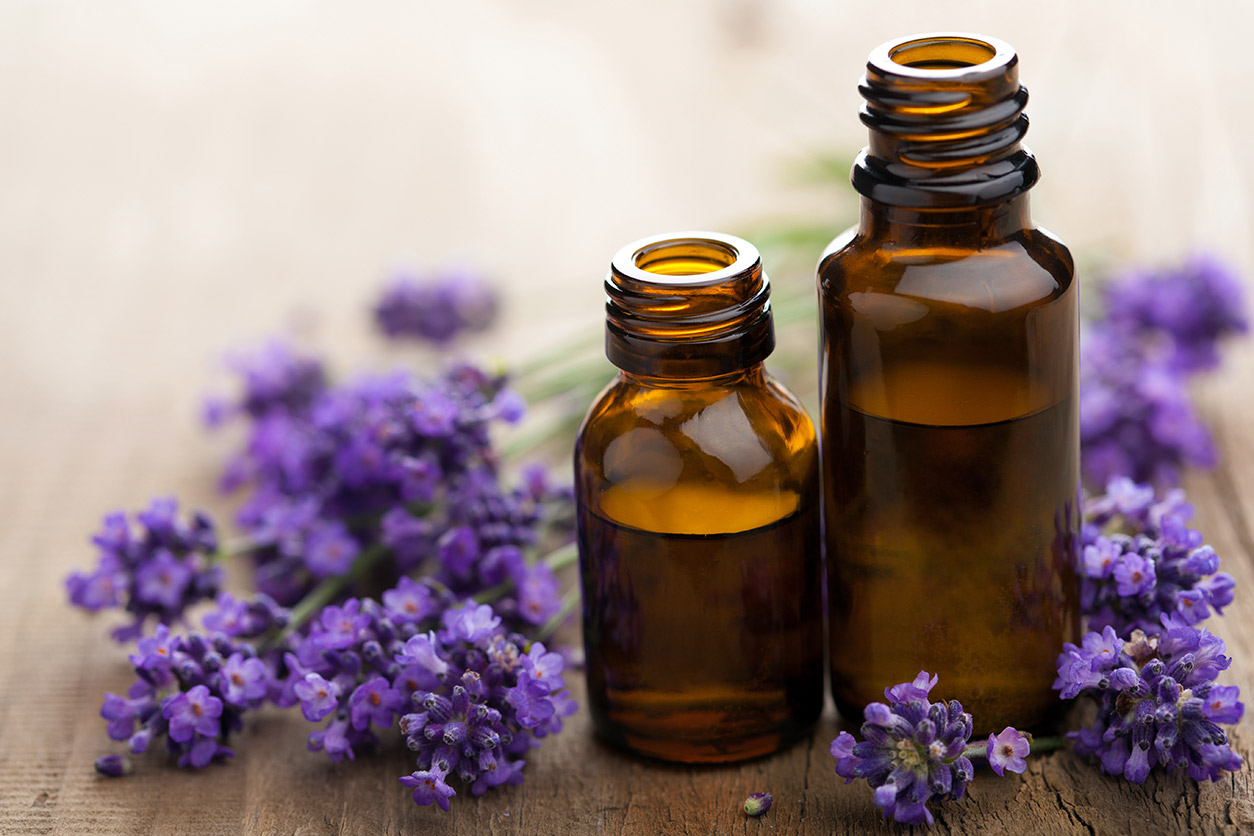 Lavender flowers and brown glass bottles of lavender oil