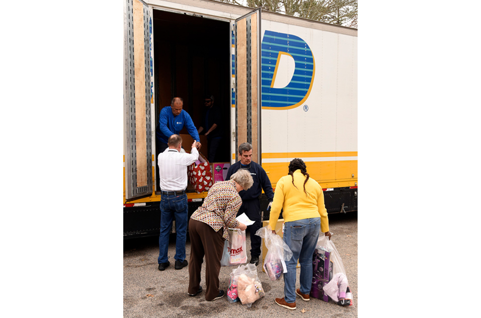 volunteers loading a truck with gifts