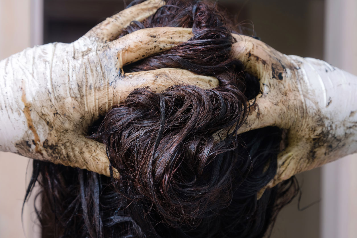 woman with gloved hands running fingers through hair and gloves coated with hair dye