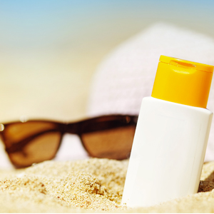 closeup of bottle of sunscreen slightly buried in sand with sunglasses and hat blurred in the background