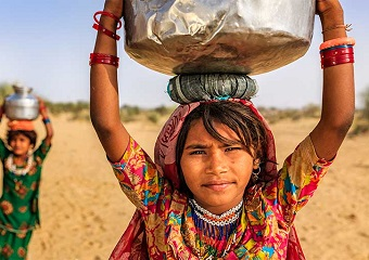 women carrying water jugs on their head