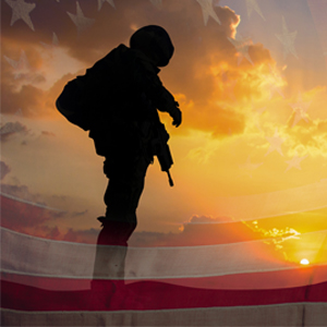 silhouette of a soldier on U.S. flag during sunset