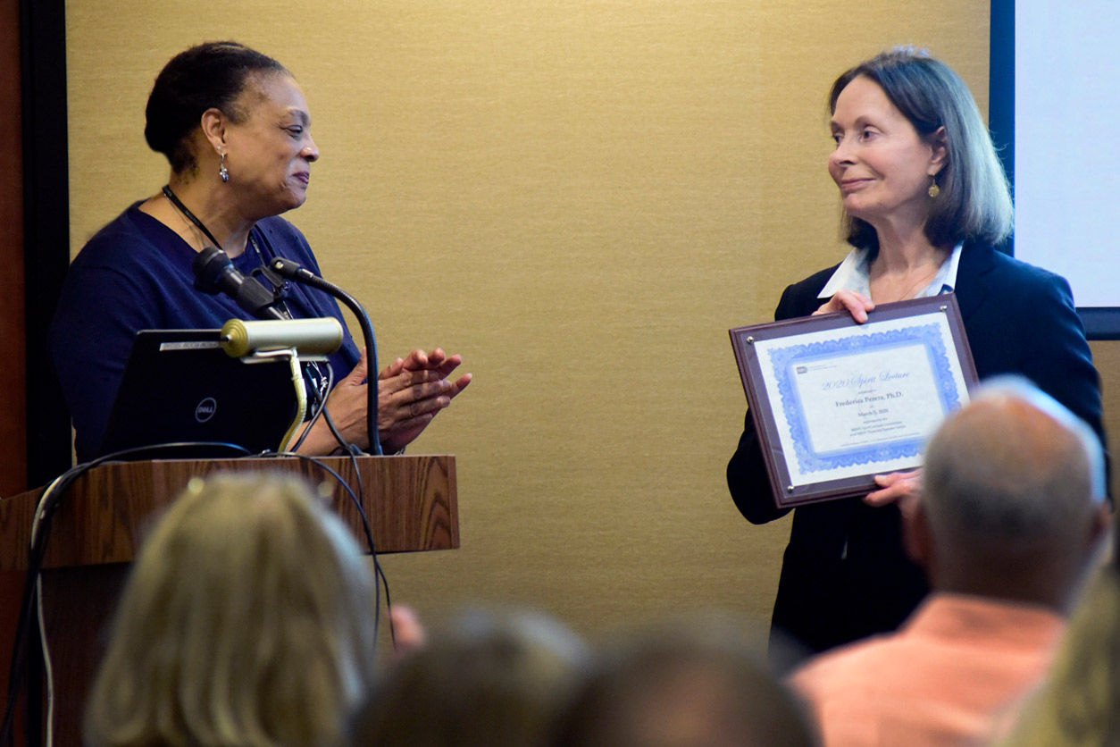 Angela King-Herbert, D.V.M. stands by Frederica Perera, Ph.D. holding an award