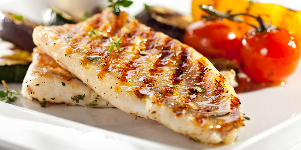 grilled fish fillet with vegetables in the background