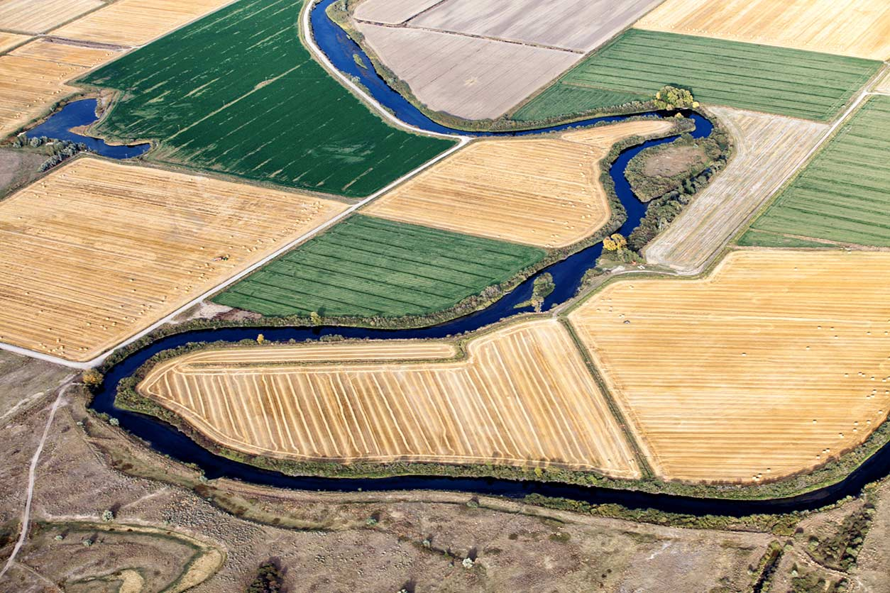 a stream meandering through farm fields