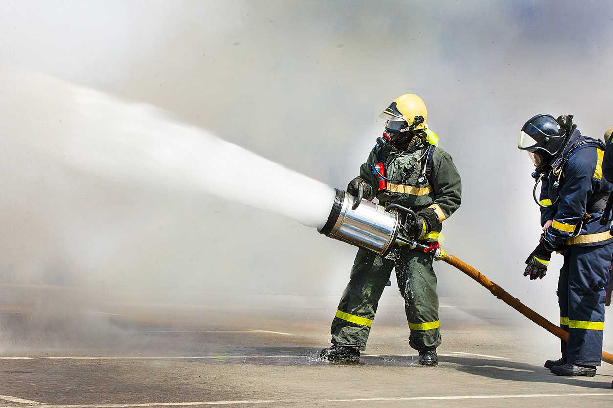 Firemen extinguish a fire with foam within the smoke