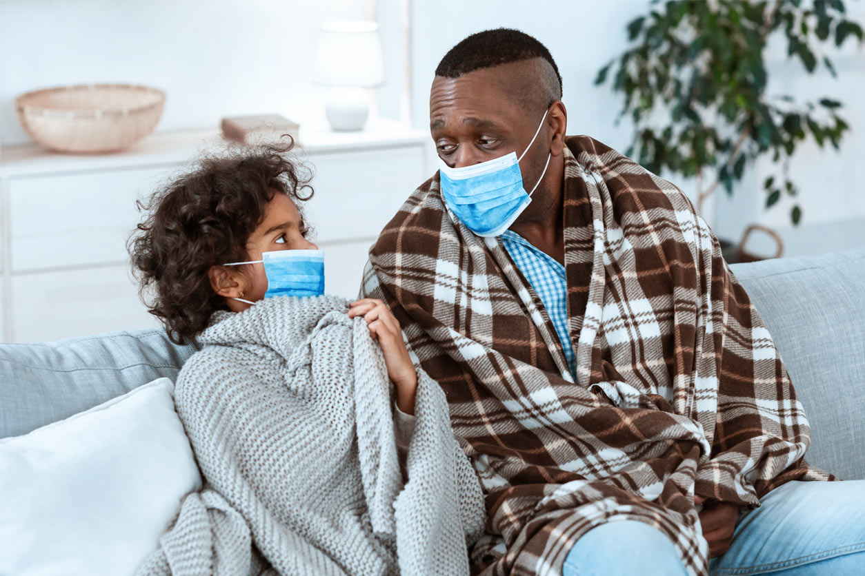 girl and a man wearing protective masks at home