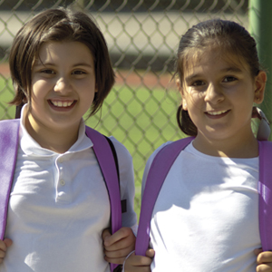 two girls smile while holding backpacks